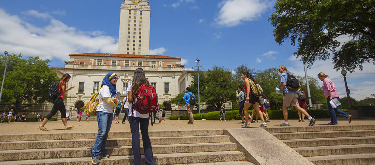 Two UT students talk on the steps of the South Mall with the UT Tower in the background.