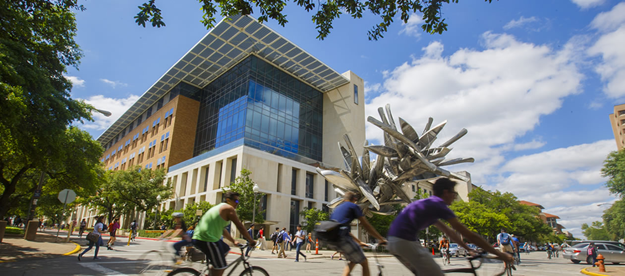 Students ride bicycles past the Norman Hackerman Building on the UT Austin campus.